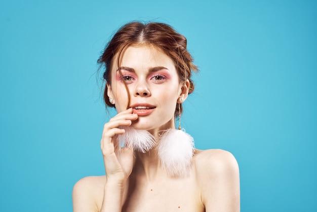 Jolie femme épaules nues maquillage lumineux boucles d'oreilles bijoux mur bleu.