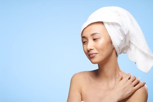Jolie femme épaules nues serviette d'aspect asiatique sur la tête fond bleu