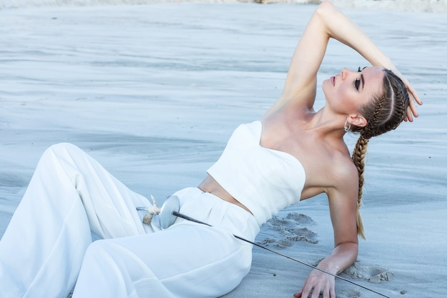 Jolie femme avec épée en tenue blanche totale. séance de mode dans le désert