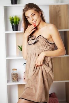 Jolie femme essayant une robe serviette et un bandage de maquillage