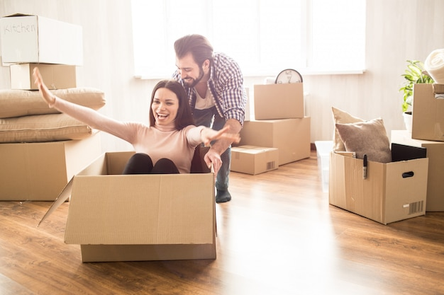 Jolie femme est assise sur la boîte. son homme la pousse pour qu'elle puisse rouler. ces gens ont l'air heureux et satisfaits