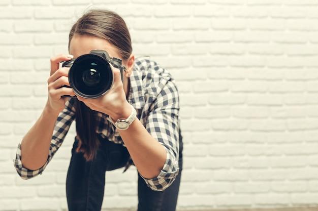 Jolie femme est un photographe professionnel avec appareil photo reflex numérique
