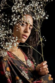 Jolie femme ethnique charmante avec des brindilles de fleurs dans l'obscurité
