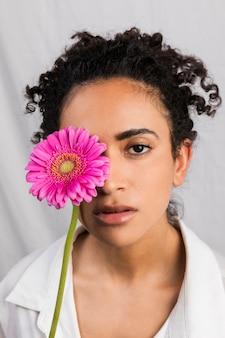 Jolie femme ethnique couvrant les yeux avec une fleur