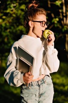 Jolie femme étudiante avec des livres posant sur la rue flou