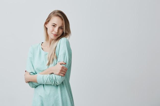 Jolie femme européenne aux cheveux longs blonds à la recherche et souriant