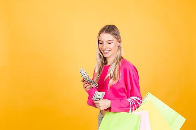 Jolie femme européenne en chemisier rose sur mur jaune