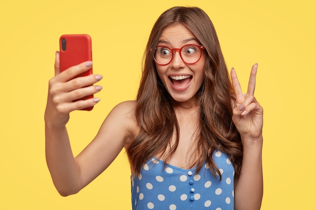 Jolie femme européenne heureuse aux cheveux longs, fait signe de paix, tient un téléphone portable, pose pour selfie, vêtue d'une robe bleue à pois, isolée sur un mur jaune fait un blog sur la vie quotidienne