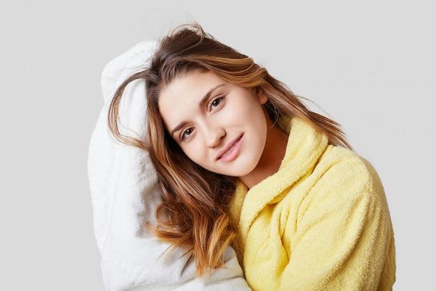 Jolie femme européenne en peignoir jaune essuie les cheveux avec une serviette