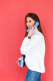 Jolie femme européenne en pull blanc décontracté heureux ludique positif holding téléphone fixe sourire ayant une conversation