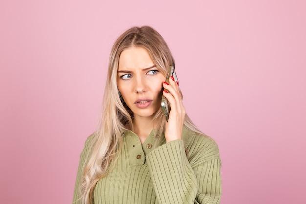 Jolie femme européenne en pull tricoté décontracté sur mur rose