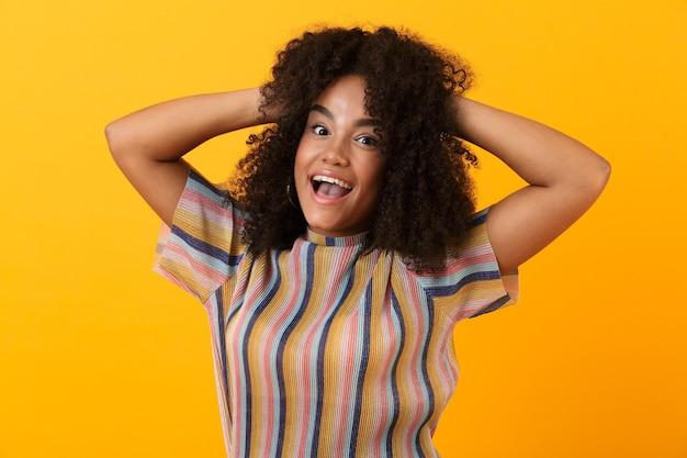 Jolie femme excitée émotionnelle isolée sur mur jaune