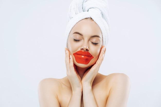 Jolie femme avec une expression calme, ferme les yeux, applique des patchs sur les lèvres, porte du maquillage naturel, une serviette enveloppée sur la tête, se tient les épaules nues à l'intérieur, fond blanc