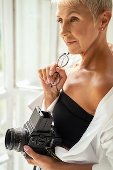 Jolie femme exprimant sa positivité, tenant la caméra dans la main gauche