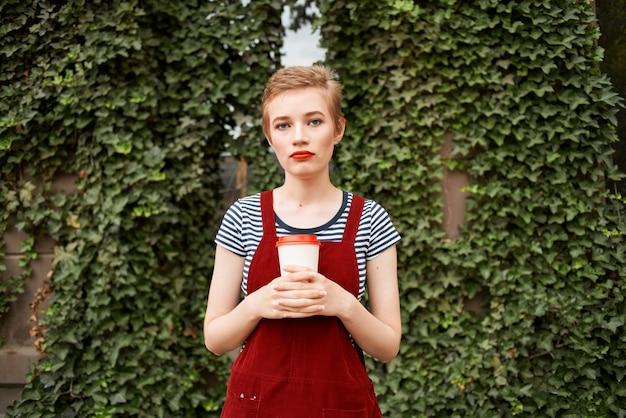 Jolie femme à l'extérieur une tasse de café promenade de loisirs