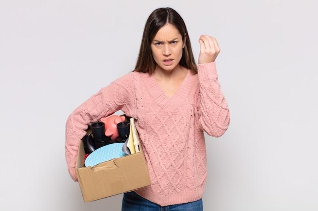 Jolie femme faisant un capice ou un geste d'argent, te disant de payer tes dettes !