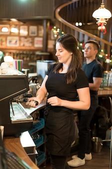 Jolie femme faisant du café au café