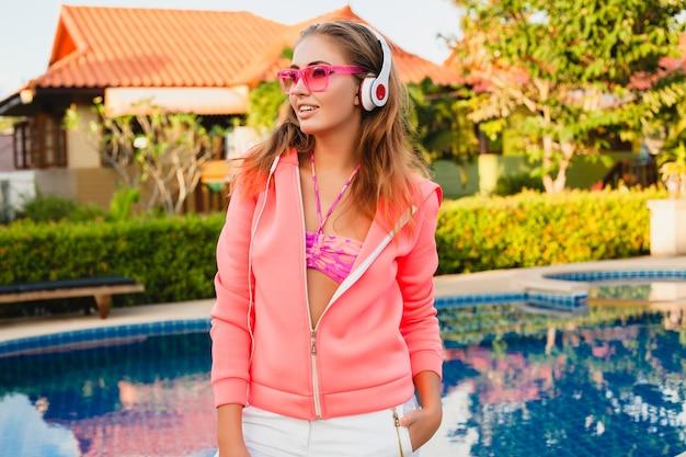 Jolie femme faisant du sport à la piscine en sweat à capuche rose coloré portant des lunettes de soleil, écouter de la musique dans les écouteurs en vacances d'été, jouer au tennis, style sport