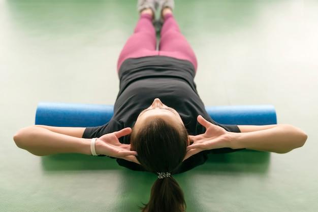 Jolie femme faisant de l'exercice de rouleau de mousse se détendre son dos et posant dans un centre de remise en forme lumineux moderne