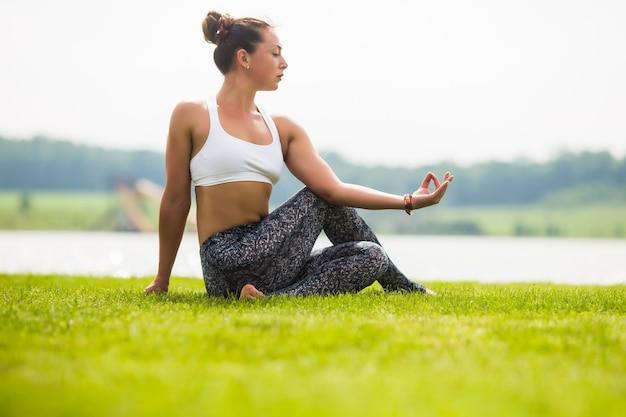Jolie femme faisant des exercices de yoga dans le parc verdoyant
