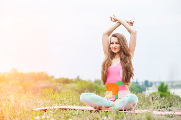 Jolie femme faisant des exercices de yoga sur la nature