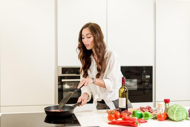 Jolie femme faisant frire la viande sur la casserole avec du vin et des légumes dans la cuisine