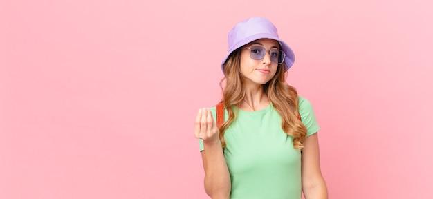 Jolie femme faisant un geste de capice ou d'argent, vous disant de payer. concept d'été