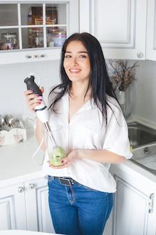 Jolie femme faisant un smoothie à l'intérieur