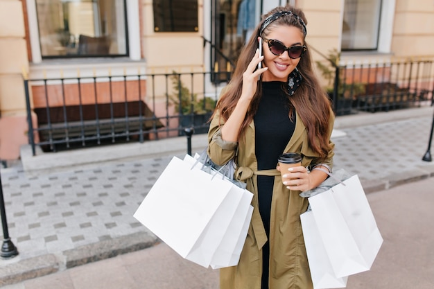 Jolie femme fashionista aux cheveux longs appelant quelqu'un pendant les courses du week-end
