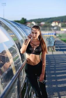 Jolie femme fatiguée fait une pause après un dur entraînement au stade. sport, concept de soins de santé.