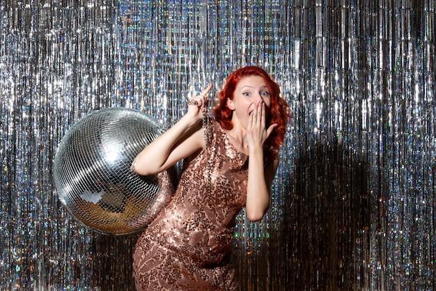 Jolie femme en fête avec boule disco sur rideaux lumineux rideaux