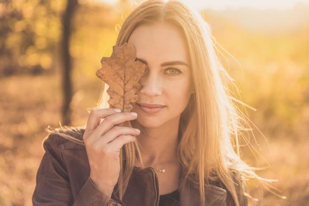 Jolie femme avec des feuilles d'automne