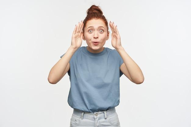 Jolie femme, fille ludique aux cheveux roux rassemblés en un chignon. porter un t-shirt bleu et un jean. jouer à cache-cache, découvrir son visage. isolé sur mur blanc