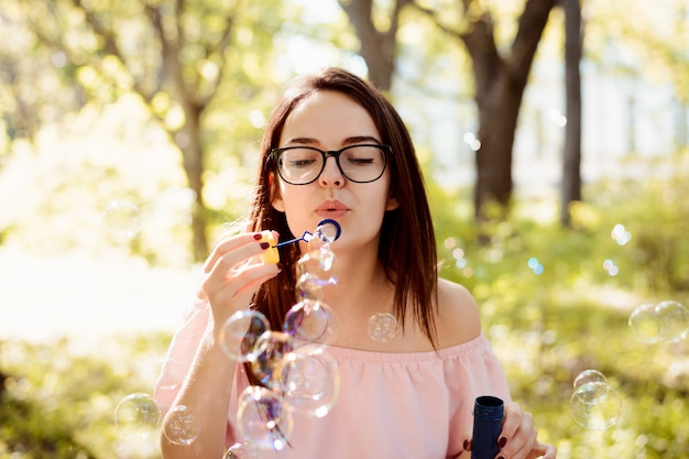 Jolie femme fille soufflant des bulles de savon dans le parc