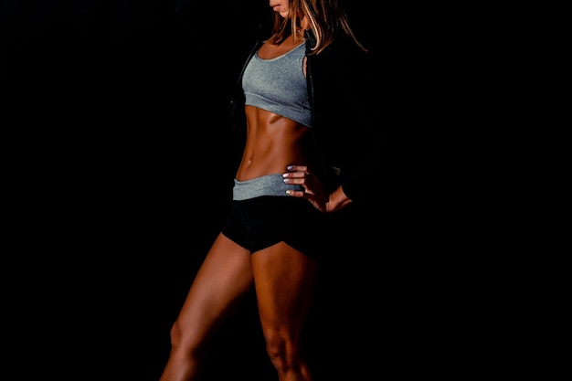Une jolie femme fléchissant son dos sur un modèle de fitness sexy fond noir dans un studio sombre