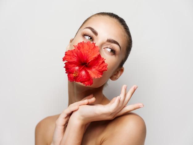 Jolie femme avec une fleur rouge dans la bouche cosmétiques glamour vue recadrée
