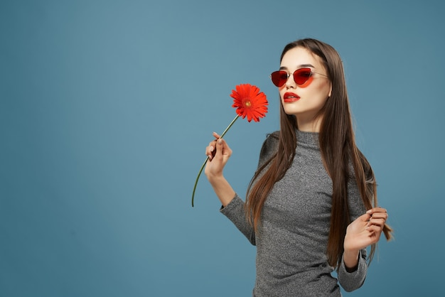 Jolie femme fleur rouge lunettes de soleil studio fond isolé. photo de haute qualité