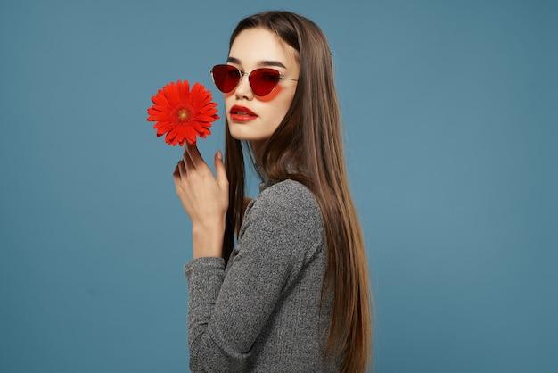 Jolie femme fleur rouge lunettes de soleil studio fond isolé