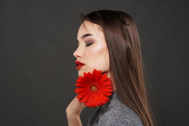 Jolie femme avec une fleur rouge de maquillage lumineux près du glamour du visage