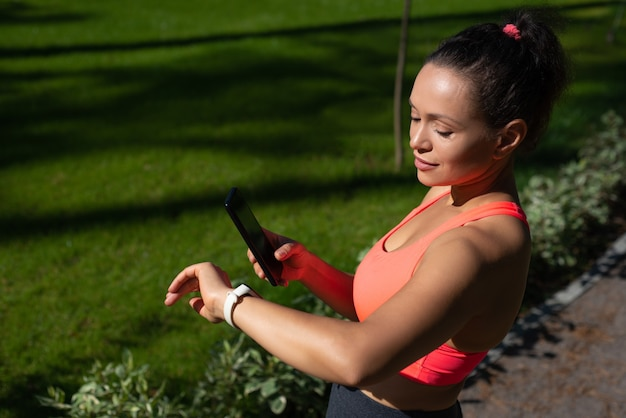 Jolie femme en forme regardant le bracelet de remise en forme et examinant comment les calories ont été perdues pendant la course