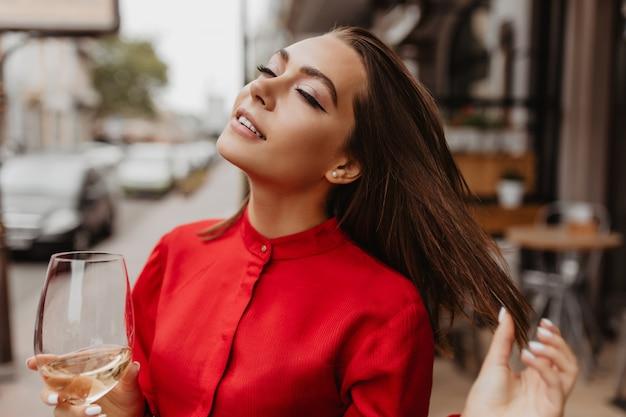 Jolie femme française en chemisier élégant rouge appréciant le goût de champagne. portrait en plein air de brune aux cheveux courts et raides