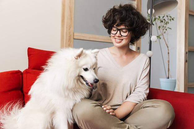 Une jolie femme frisée assise sur un canapé avec son chien blanc cutie.