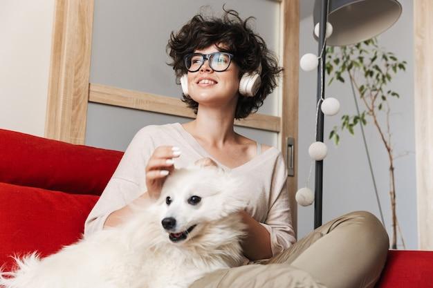 Une jolie femme frisée assise sur un canapé avec son chien blanc mignon écoute de la musique avec des écouteurs.