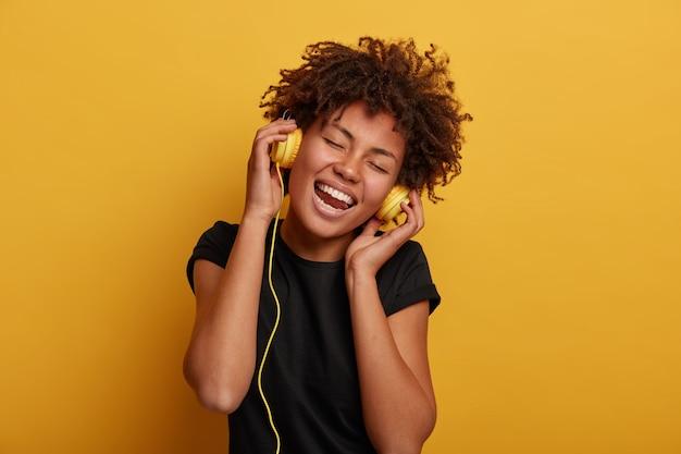 Jolie femme frisée avec des sourires à pleines dents, garde les mains sur le casque, vêtu d'un t-shirt noir, isolé sur fond jaune