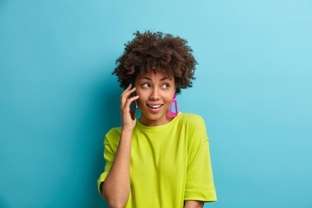 Jolie femme gaie aux cheveux bouclés a des conversations téléphoniques via téléphone mobile a une expression heureuse