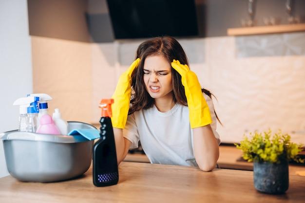 Jolie femme en gants jaunes protecteurs a mal à la tête dans la cuisine pendant le nettoyage et ne l'aime pas du tout