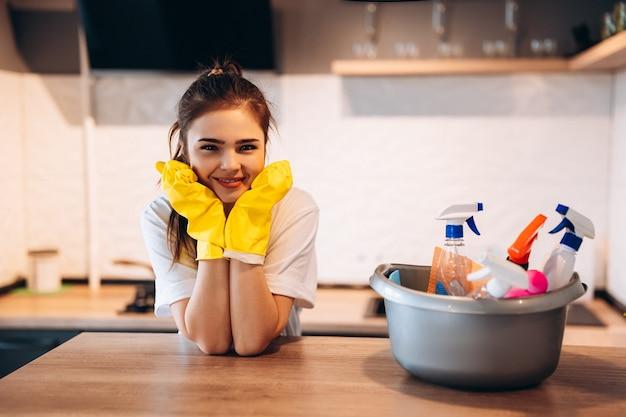 Jolie femme en gants jaunes de protection sourit dans la cuisine pendant le nettoyage