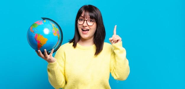 Jolie femme grande taille se sentant comme un génie heureux et excité après avoir réalisé une idée, levant joyeusement le doigt, eurêka !