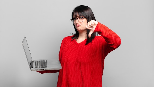 Jolie femme grande taille se sentant fâchée, en colère, agacée, déçue ou mécontente, montrant les pouces vers le bas avec un regard sérieux