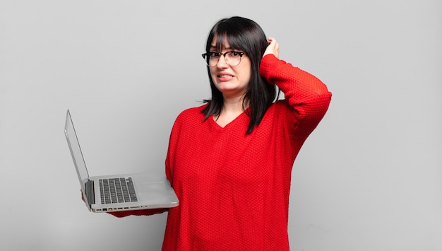 Jolie femme de grande taille se sentant stressée, inquiète, anxieuse ou effrayée, les mains sur la tête, paniquée par erreur